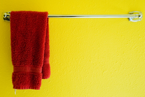 Red towel hanging on towel rack in front of a yellow wall
